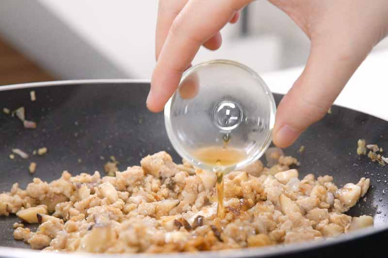 加入生抽、老抽、砂糖、麻油及1汤匙水炒匀。