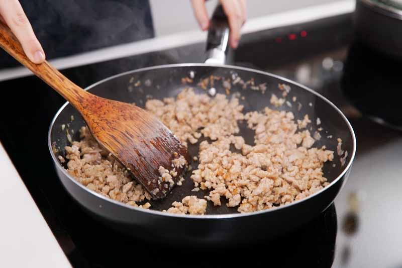 加入猪肉末炒至熟透,加入香菇炒匀。