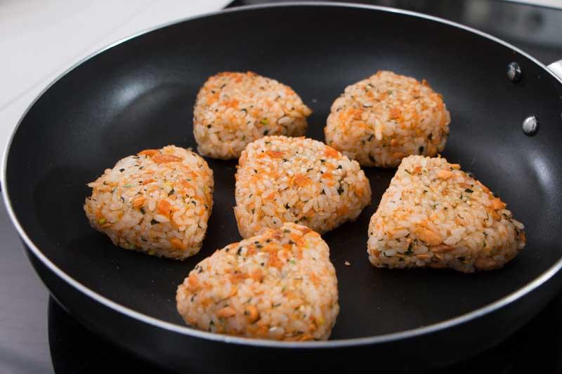 用中火烧热锅,用厨房纸抹上一层油,放入饭团,煎至两面稍微上色。